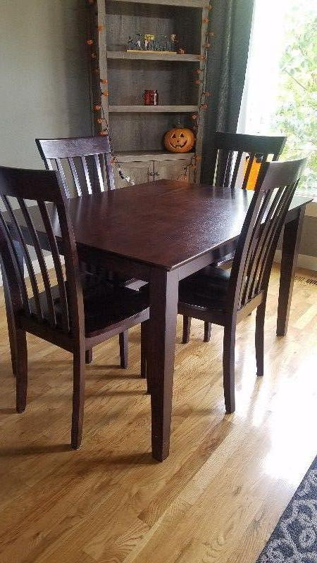 Dark brown wood dining table with four chairs